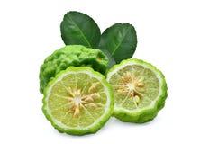 Totalité et demi bergamote fraîche avec des feuilles de vert d'isolement Images stock