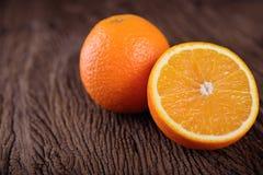 Totalité et demi orange navel de coupe sur le fond en bois Photographie stock