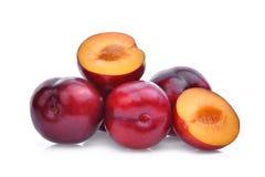 Totalité et moitié des prunes de cerise rouges d'isolement sur le blanc Photo stock