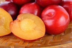 Totalité et prune rouge de demi golfe frais de coupe dans le panier en bambou Photos stock