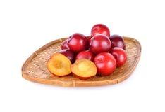 Totalité et prune rouge de demi golfe frais de coupe dans le panier en bambou Image stock