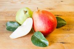 Totalité et tranche de poires mûres et de poire verte Photographie stock