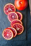 Totalité et tranches d'oranges sanguines sur un fond noir d'ardoise C image stock