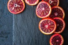 Totalité et tranches d'oranges sanguines sur un fond noir d'ardoise C images stock