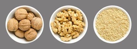 Totalité, noix, moitiés de noyau et noix moulues dans des cuvettes blanches sur le fond gris images stock