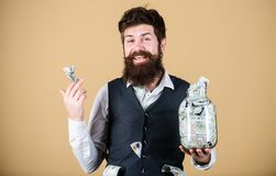 He is totally rich. Bearded rich man with large amount of money cash. Rich businessman keeping money in glass jar. Rich. And money monger royalty free stock photos
