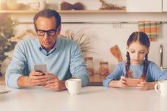 Totalt absorberad flicka och hennes farsa som hemma använder smartphones Royaltyfri Foto