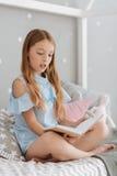 Totalt absorberat i läs- flickasammanträde på säng Royaltyfria Foton