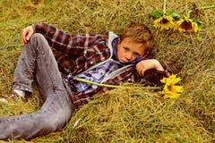 Totalt bekymmerslöst Den lilla pojken kopplar av i hayloft Liten pojke i lantgårdladugård Hayloft i bygd Precis koppla av royaltyfri fotografi