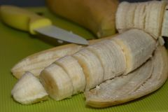 Totalview of a banana with some banana slices with kitchen decoration. Close up of a banana with some banana slices with kitchen decoration photographed with Royalty Free Stock Images