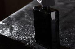Totaly black bottle of masculine elegent fragrance on black leather background. Black bottle of expensive fragrance on black leather and water drops on it stock photography