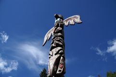 Totem pole. Low angle view of traditional native Indian totem pole with blue sky and cloudscape background stock photos