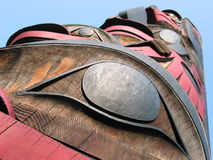 Totem pole. Carved in wood with sky in the background - detail Royalty Free Stock Photo