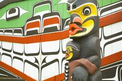Totem Pole. A totem pole stands infront of a painted background Royalty Free Stock Image