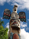 Totem pole. Carved in wood with sky background Royalty Free Stock Photos