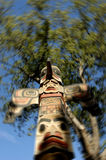 Totem Pole. Indian totem pole with blurred trees on background. Selective focus royalty free stock image