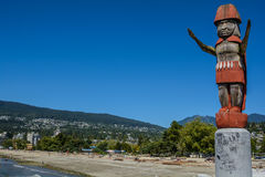 Totem pole against the background of mountains. On the North Vancouver Stock Image