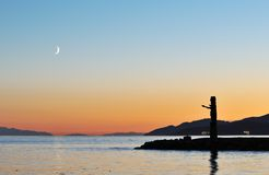 Totem pole and crescent moon Royalty Free Stock Photography