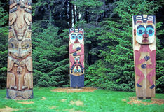 Totem poles in Alaska. These totem poles are photographed in the Sitka historical park in Sitka, Alaska.  This picture is from a scanned slide Royalty Free Stock Photo