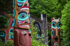 Totem Poles Near Saxman Tribal House. Detail of totem pole at Saxman Village tribal house near Ketchikan Alaska with Sun Raven in background Stock Photography