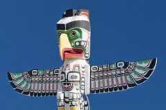 A totem wood pole in the blue cloudy background. In British Columbia Canada stock images