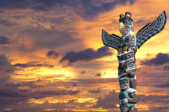 A totem wood pole in the gold cloudy background. Isolated totem wood pole in the gold sunset background Stock Photo