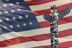 Totem wood pole ion usa flag background. Isolated totem wood pole on america star and stripes flag background stock photography