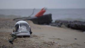 Toter Astronaut auf dem Planeten Der Schädel vom Kopf im Sturzhelm liegt auf dem Sand durch das Meer Zufällig beunruhigt stock footage