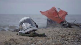 Toter Astronaut auf dem Planeten Der Schädel vom Kopf im Sturzhelm liegt auf dem Sand durch das Meer Zufällig beunruhigt stock video footage