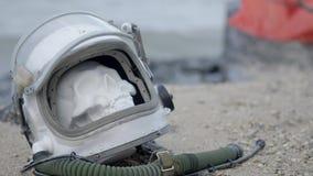Toter Astronaut auf dem Planeten Der Schädel vom Kopf im Sturzhelm liegt auf dem Sand durch das Meer Zufällig beunruhigt stock video