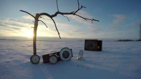 Toter Baumast, alte Uhren auf Schnee und Sonnenaufgang, Zeitspanne 4K