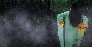 Totes Mädchen mit Jack-O-Laterne in einem nebelhaften Wald nachts stockbild