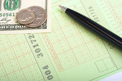 Totolizator ticket. Close up of sports betting slip, pen, coins and banknotes Stock Images