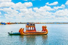 Totora boat on Titicaca lake in Peru. Titicaca lake, Puno, Peru - March, 20, 2017. Traditional Totora boat with tourists near Uros floating islands on Titicaca Stock Photography