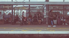 Tottenham Hale station in London, vintage look. LONDON, UK - CIRCA JUNE 2016: People waiting for transport at Tottenham Hale station platform, vintage looking Royalty Free Stock Photo