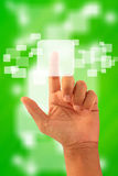 Touch on. One hand on green touchscreen Royalty Free Stock Images