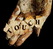 Touch. Female hand textured with dry lichen holding the word touch Royalty Free Stock Photo