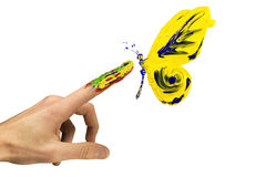 Touch between finger and painted yellow butterfly Royalty Free Stock Images