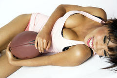 Happy Girl Rolls on Ground Embracing Football stock images