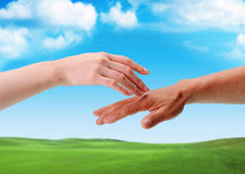 The Touch Of Hands Between Man And Woman. In front of a green field Royalty Free Stock Images