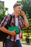 In touch with his friends. Handsome male student talking on the mobile phone and smiling while walking outdoors Stock Photo