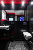 Touch of luxury in bathroom. Functional bathroom with black tiles, red details, mirror, white basin and toilet Royalty Free Stock Photography