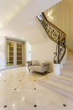 A touch of luxury in new hallway. Light hallway with glossy tiles and beautiful staircase Royalty Free Stock Photos