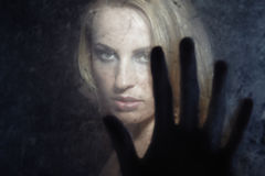Touch me. Portrait of the woman indoors behind the dirty glass and touching by the fingers Stock Photo
