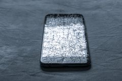 Touch, modern black mobile phone with a broken screen. A lot of cracks on the screen of a mobile phone royalty free stock photography