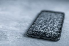 Touch, modern black mobile phone with a broken screen. A lot of cracks on the screen of a mobile phone royalty free stock photo