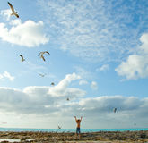 In touch with nature. Standing on the beach, a child is raising his hands up and reaching for the sky Stock Image