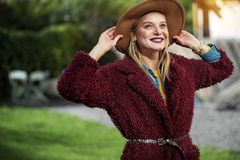 Joyful blond girl enjoying natural landscape outdoor. In touch with nature. Portrait of excited young woman admiring nature in the park. She is touching her hat Stock Photography