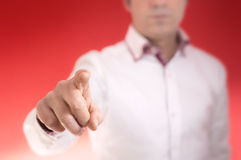 Touch nothing on red faded. A man touching an invisible interface with his finger with a red faded background. Place you own graphics stock photo