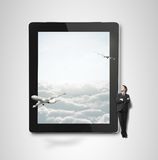 Touch pad with airplane. Businessman looking at big  touch pad with airplane Royalty Free Stock Images